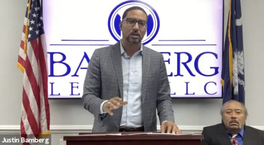 n this screen grab from video provided by Bamberg Law, LLC, attorney Justin Bamberg, standing, speaks at a news conference as plaintiff Jethro DeVane, seated at right, listens, Tuesday, Dec. 22, 2020, in Orangeburg, S.C. DeVane was embarrassed and feared for his life during a June 2019 episode when a Rock Hill police officer looking for teens who might have been breaking into cars held him outside naked and at gunpoint after he peeked out his door to check on the disturbance. (Courtesy of Bamberg Law, LLC via AP)