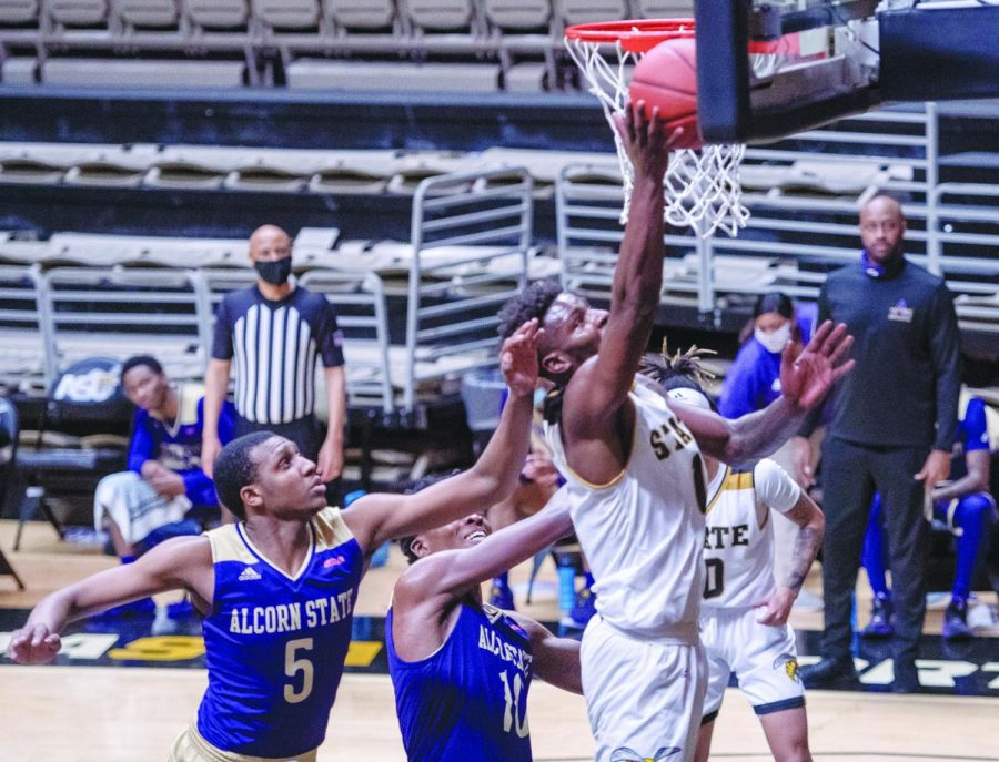 Alabama State University Hornet Brandon Battle competing on the boards against two Alcorn State University Brave defenders.