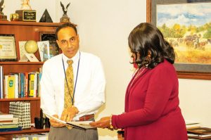 Deputy Superintendent of Education Daniel Boyd explains some new procedures to his administrative assistant.