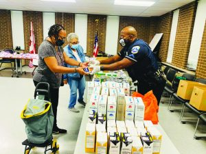 Perry Morgan, Jr. passes out food items to people in the Washington D. C. area who have come to the food bank for necessities.  Morgan said that he chooses to educate the communities that he patrols rather than to charge them. He hears them out, learns their stories, acknowledges their needs and courteously lets the public know that the Metro Police Department is not against them as people.