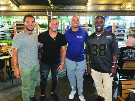 Before sitting down to enjoy lunch, alumnus Orlando Arnold (third from left) takes a moment to pose with the professional athletes that he represents.  Those athletes are Anthony Gomez who is a member of the Washington Nationals Organization, Rusber Estrada, a member of the Atlanta Braves Organization, and (far right) Jonathan Ward, a running back for the Arizona Cardinals.
