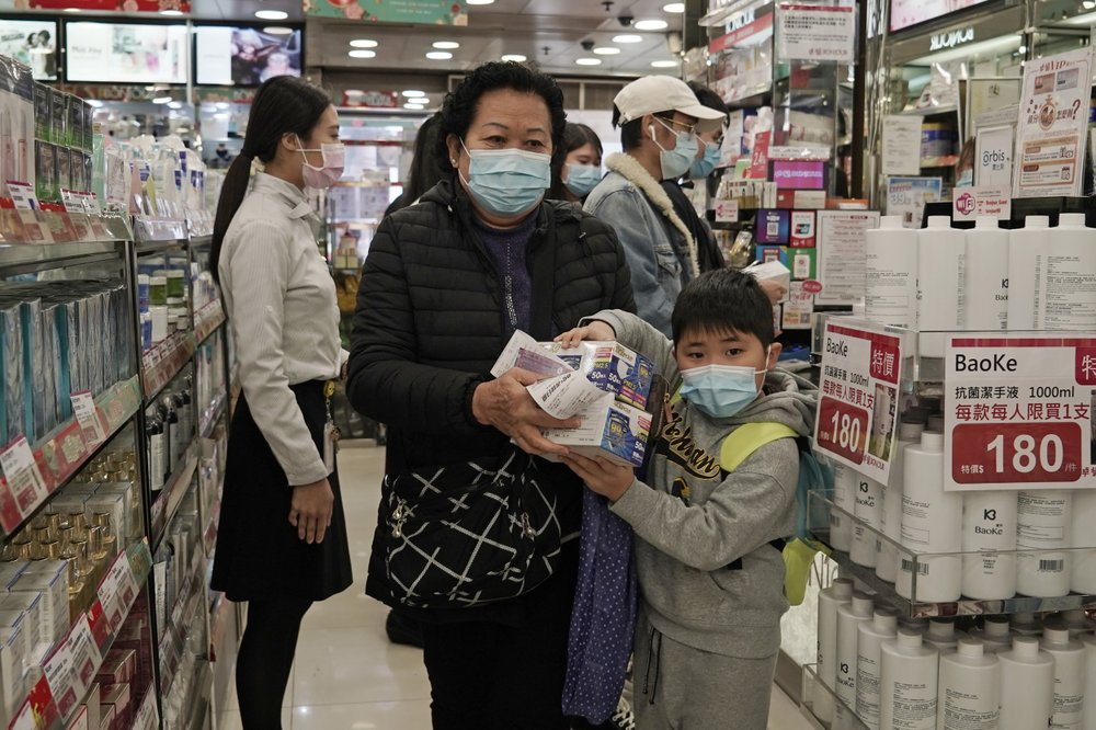 """A woman a boy purchase face masks in Hong Kong, Saturday, Feb, 1, 2020. China's death toll from a new virus has risen over 250 and a World Health Organization official says other governments need to prepare for""""domestic outbreak control"""" if the disease spreads."""