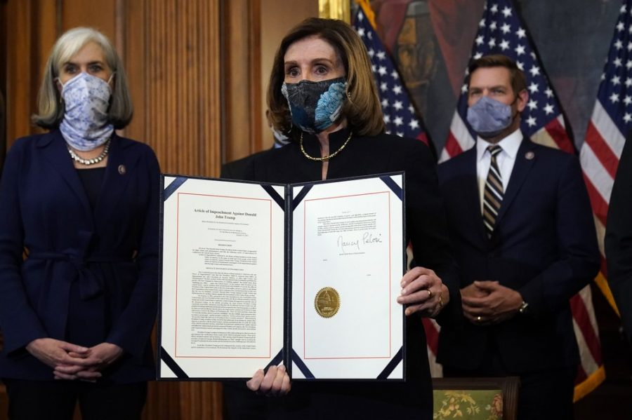 House Speaker Nancy Pelosi of Calif., displays the signed article of impeachment against President Donald Trump in an engrossment ceremony before transmission to the Senate for trial on Capitol Hill, in Washington, Wednesday, Jan. 13, 2021. (AP Photo/Alex Brandon)