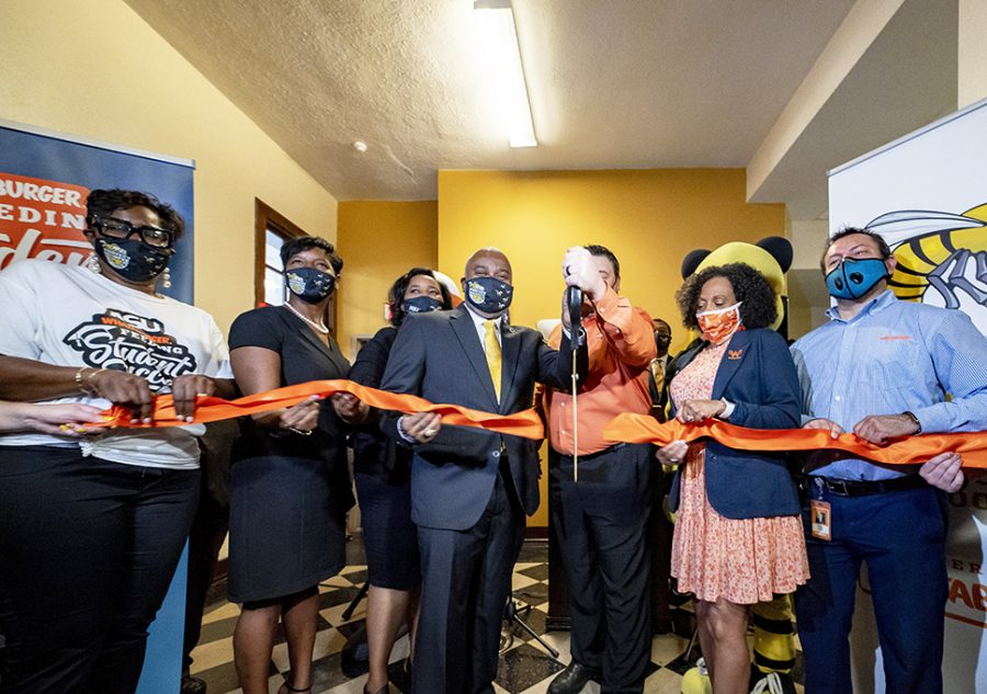 Whataburger+rep%2C+trustee%2C+university+administrators%2C+staff+and+faculty+cut+the+ribbon+during+the+opening+of+the+Resource+Room