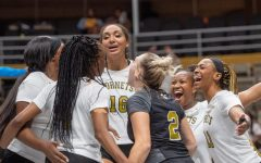 Alabama State University Hornets' middle blocker Alexis Ratliff spikes the ball over two Auburn Tigers players in a five-set thriller.