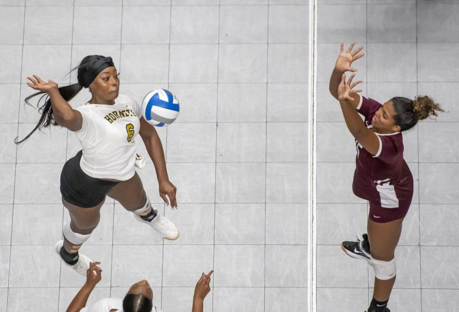 Junior middle blocker, Mahogany Vinson spikes the ball past a Bulldogs player, en-route to a sweep in their home opener.